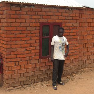 john outside house built with skills learnt at KAYD