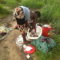 A woman washing clothes near the pond